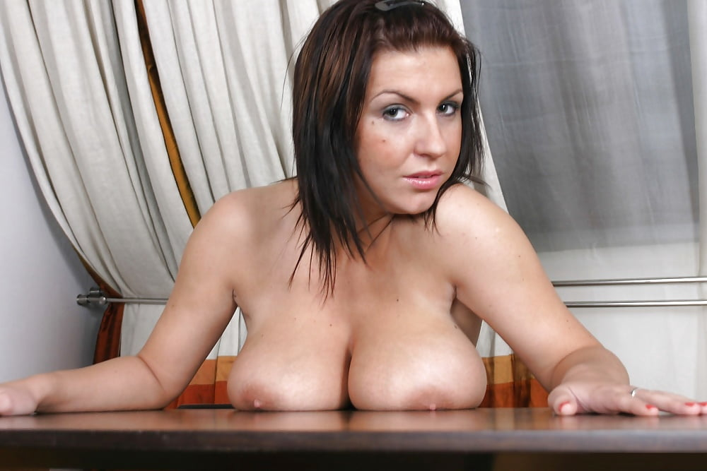 Resting her big mature tits on the table