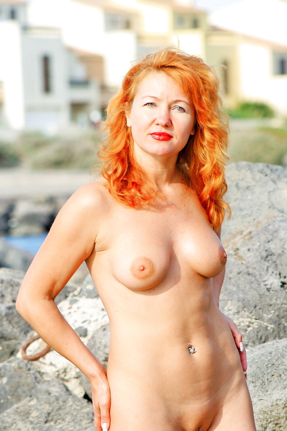 Nude mature woman with red hairstyle exposes her sexy beaver