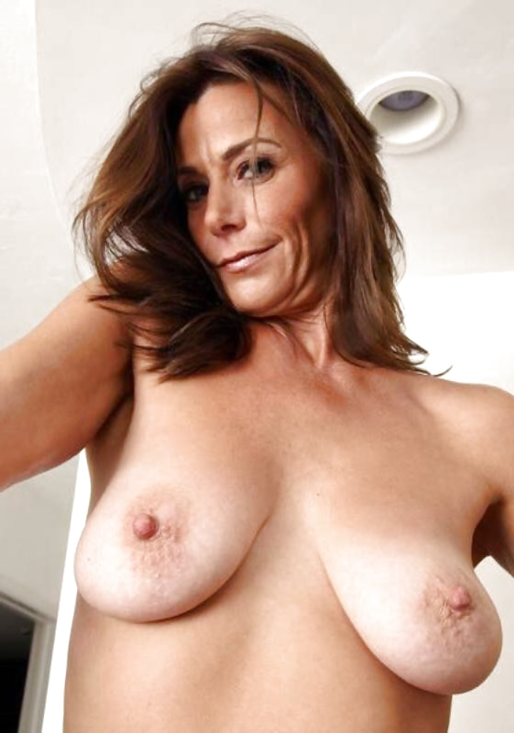 Naked big breasted milf on couch