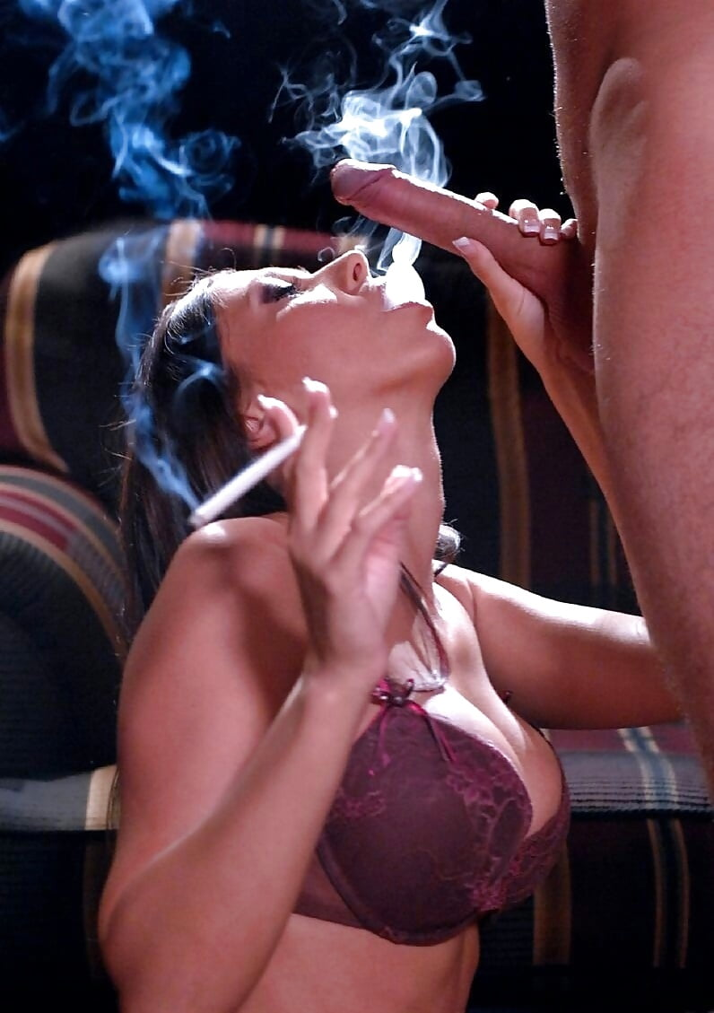 This busty brunette shows her pussy and tits while smoking a cigarette