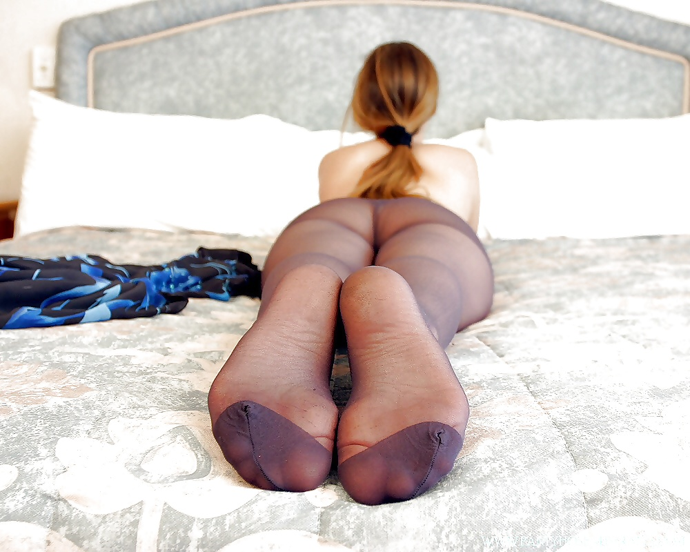 Sexy schoolgirl in black pantyhose shows off legs, feet, ass
