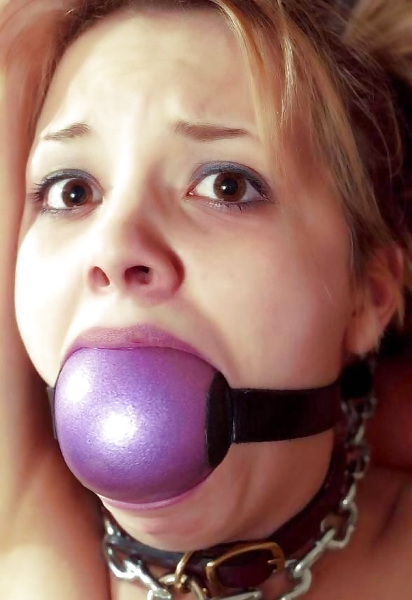 Submissive woman with ball gag in her mouth taking bdsm selfie